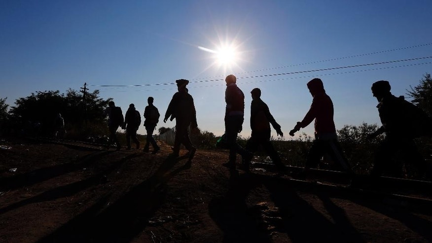 FILE - In this Sept. 9, 2015 file photo migrants cross the Hungarian-Serbian border near Roszke, southern Hungary. People crammed into boats and trekking across borders have become the dominant images of Europe's migrant crisis. In the shadows, however, there are those who are profiting, for whom every migrant is a business opportunity. (AP Photo/Matthias Schrader, file)