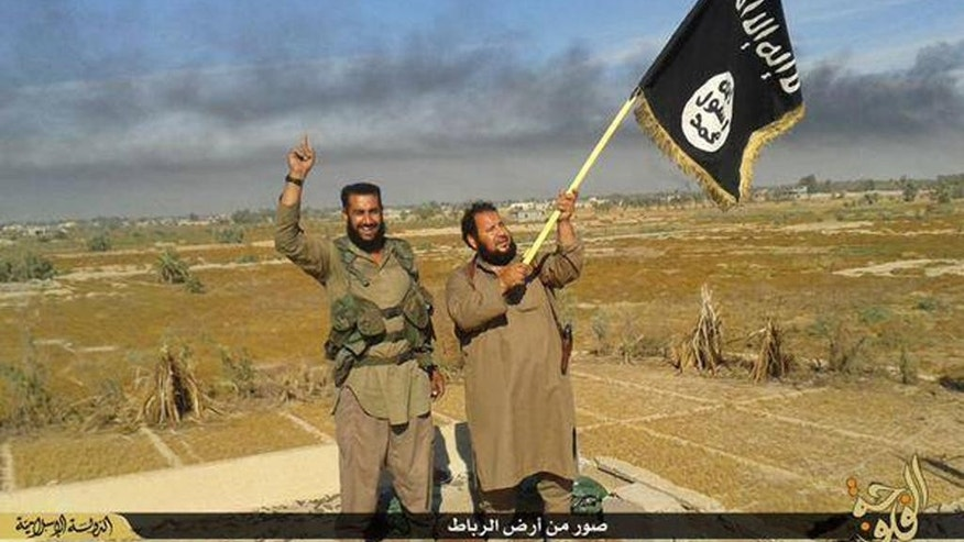"FILE - In this photo released on Sunday, June 28, 2015, by a website of Islamic State militants, an Islamic State militant waves his group's flag as he and another celebrate in Fallujah, Iraq, west of Baghdad. When world leaders convene for the U.N. General Assembly debate Monday, Sept. 28, 2015, it will be a year since the U.S. president declared the formation of an international coalition to ""degrade and ultimately destroy"" the Islamic State group. Despite billions of dollars spent and thousands of airstrikes, the campaign appears to have made little impact. (Militant website via AP, File)"