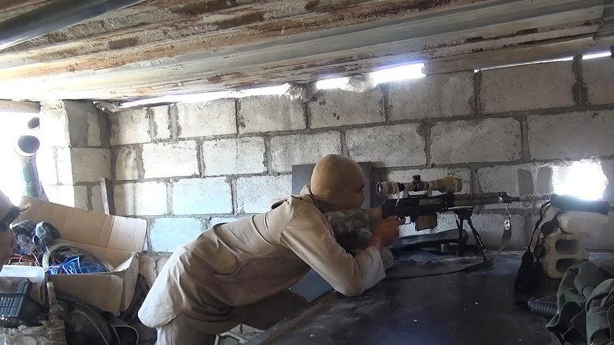 "FILE - This picture released on July 13, 2015 by the Rased News Network, a Facebook page affiliated with Islamic State militants, shows an Islamic State militant sniper in position during a battle against Syrian government forces in Deir el-Zour province, Syria. When world leaders convene for the U.N. General Assembly debate Monday, Sept. 28, 2015, it will be a year since the U.S. president declared the formation of an international coalition to ""degrade and ultimately destroy"" the Islamic State group. Despite billions of dollars spent and thousands of airstrikes, the campaign appears to have made little impact. (Rased News Network via AP, File)"