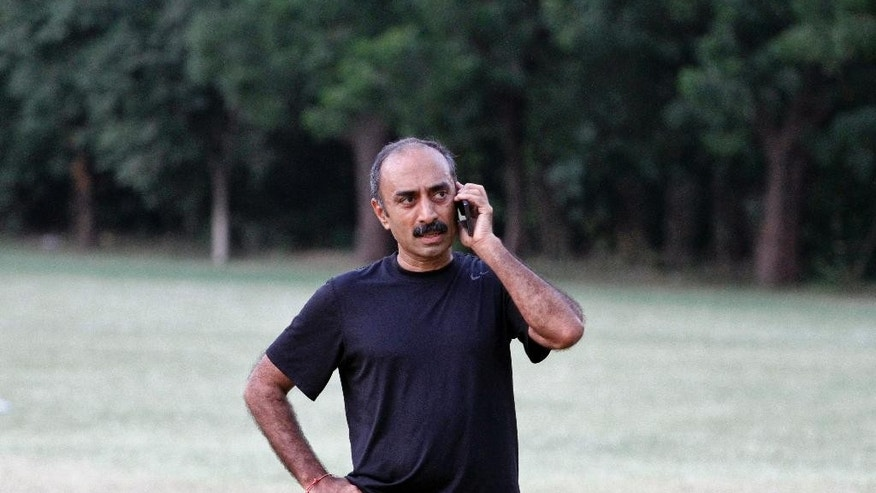 In this Sept. 9, 2015 photo, Sanjiv Bhatt, Indian officer with the intelligence bureau in the western state of Gujarat during the 2002 riots, speaks on his mobile phone in Ahmadabad, India. Since Narendra Modi took office last year, more than 9,000 humanitarian and human rights groups have lost their registration to receive foreign funding, effectively shutting many down, and dozens of activists have been threatened with arrest. (AP Photo/Ajit Solanki)