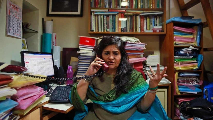 In this Sept. 7, 2015 photo, Teesta Setalvad, a rights activist fighting for scores of survivors and victims of India's western state of Gujarat riots, speaks on phone during an interview with The Associated Press at her office in Mumbai, India. ISince Narendra Modi took office last year, more than 9,000 humanitarian and human rights groups have lost their registration to receive foreign funding, effectively shutting many down, and dozens of activists have been threatened with arrest. (AP Photo/Rafiq Maqbool)