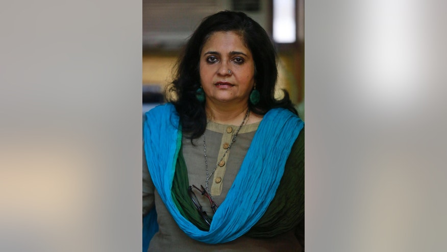 In this Sept. 7, 2015 photo, Teesta Setalvad, a rights activist fighting for scores of survivors and victims of India's western state of Gujarat riots, poses for photographs at her office in Mumbai, India. Since Narendra Modi took office last year, more than 9,000 humanitarian and human rights groups have lost their registration to receive foreign funding, effectively shutting many down, and dozens of activists have been threatened with arrest. (AP Photo/Rafiq Maqbool)