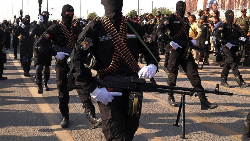 Armed members of the Abbas combat squad, a Shiite militia group, march in a military parade in Basra, 340 miles (550 kilometers) southeast of Baghdad, Iraq, Saturday, Sept. 26, 2015. Iraqi security forces and allied Shiite militias are training together to try to regain Iraqi cities under Islamic State control, officials said. (AP Photo/Nabil al-Jurani)