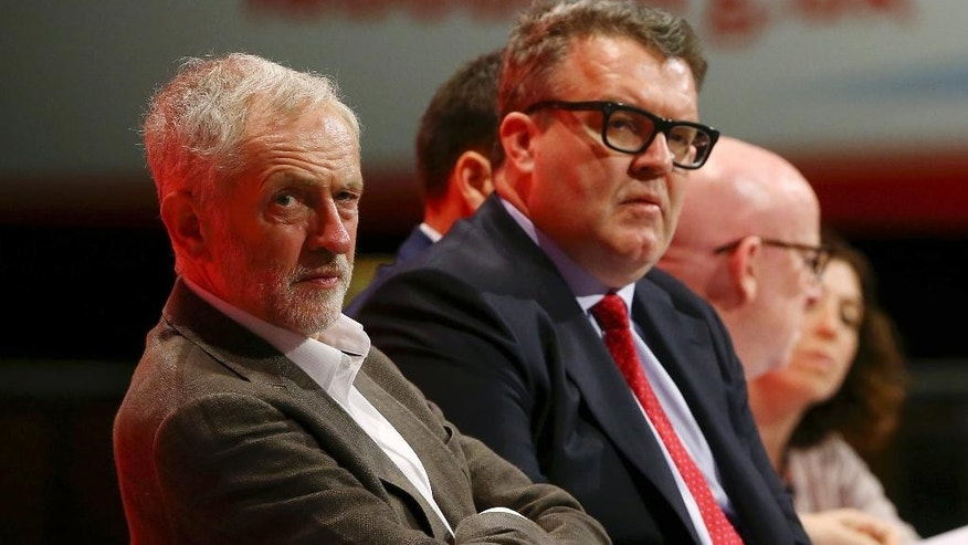 Britain's Labour party leader Jeremy Corbyn, left, with deputy leader Tom Watson, centre,  listen to speeches during the Labour Party annual conference at the Brighton Centre in Brighton, England, Sunday Sept. 27, 2015. For six decades, British governments have considered unilateral nuclear disarmament unthinkable, but the newly elected radical left-wing leader Corbyn, and his party members may commit a future Labour government to scrapping Britain's Trident nuclear arms program. (Gareth Fuller / PA via AP) UNITED KINGDOM OUT - NO SALES - NO ARCHIVES
