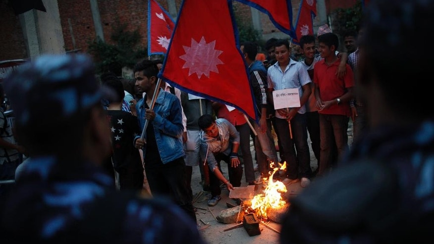 Students affiliated with Communist Party of Nepal (Unified Marxist–Leninist), make a fire near the Indian Embassy during a protest against the blockade of cargo trucks along the border with India in Kathmandu, Nepal, Sunday, Sept. 27, 2015. Nepal started imposing restrictions on vehicular movement Sunday as a blockade of cargo trucks along the border with India has badly hit the supplies of essential commodities, especially fuel. (AP Photo/Niranjan Shrestha)