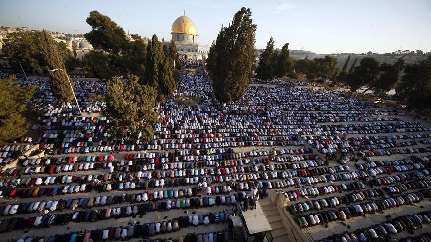 FILE - In this Thursday, Sept. 24, 2015. file photo, Palestinians pray during the Muslim holiday of Eid al-Adha, near the Dome of the Rock Mosque. Israeli police are reporting new unrest at Jerusalem's most sensitive holy site  Sunday, Sept. 27, 2015. The site, known as the Temple Mount to Jews and the Noble Sanctuary to Muslims, had experienced several days of unrest in recent weeks. (AP Photo/Mahmoud Illean, File)