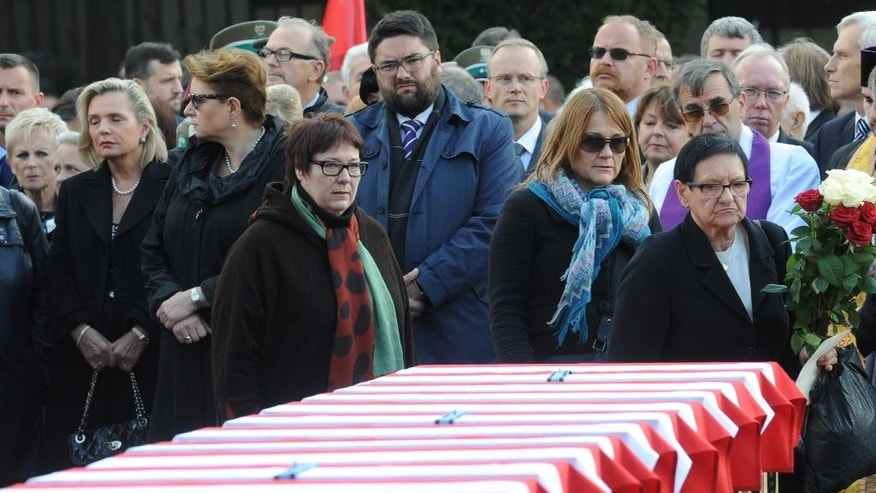 Officials and family members gather in front of coffins during the first burials of World War II heroes who were later secretly slain by the communists, at the Powazki cemetery in Warsaw, Poland, Sunday, Sept. 27, 2015. Remains of 35 Polish soldiers with bullet holes through the back of the skull were buried after being recently recovered from unmarked mass graves. (AP Photo/Alik Keplicz)