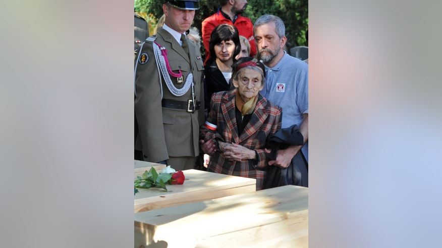 Family members look at coffins during the first burials of World War II heroes who were later secretly slain by the communists, at the Powazki cemetery in Warsaw, Poland, Sunday, Sept. 27, 2015. Remains of 35 Polish soldiers with bullet holes through the back of the skull were buried after being recently recovered from unmarked mass graves. (AP Photo/Alik Keplicz)