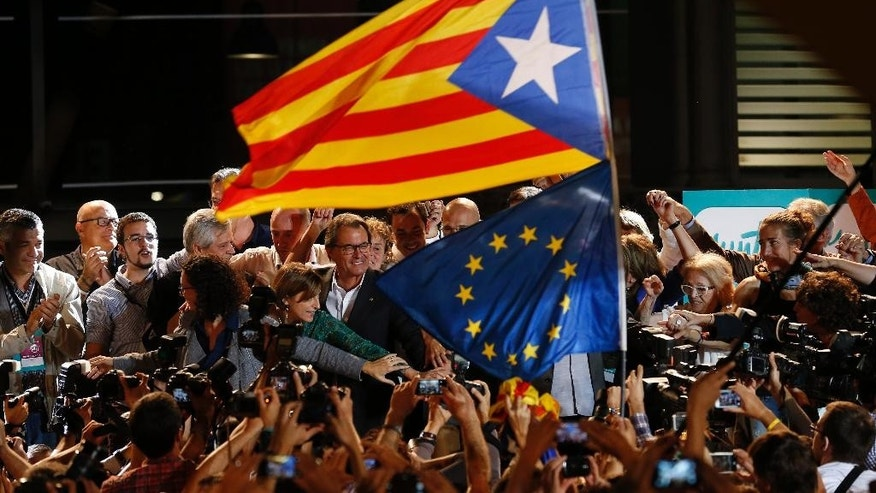 "A ""estelada"" or pro independence flag and a European Union flag are waved in front of the President of Democratic Convergence of Catalonia Artur Mas, center in front of supporters in Barcelona, Spain, Sunday Sept. 27, 2015. Voters in Catalonia participated in an election Sunday that could propel the northeastern region toward independence from the rest of Spain or quell secessionism for years. An exit poll predicts that pro-independence parties in Spain's Catalonia region are likely to win a majority of seats in the regional parliament, but it's unclear whether they would be able to come together to push together on a plan to secede from Spain. (AP Photo/Manu Fernandez)"