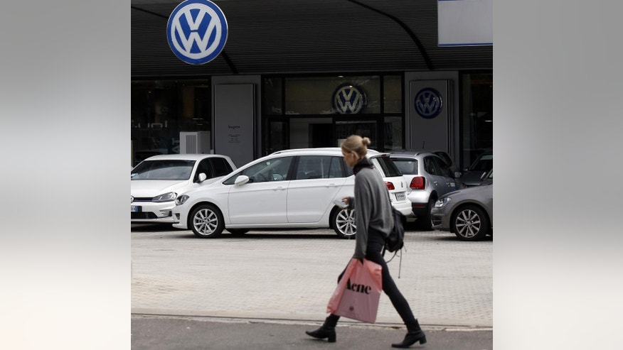 A woman walks by a Volkswagen dealer in Milan, Italy, Sunday, Sept. 27, 2015. German media report that Volkswagen received warnings years ago about the use of illegal tricks to defeat emissions tests. The automaker admitted last week that it used special software to fool U.S. emissions tests for its diesel vehicles. (AP Photo/Luca Bruno)