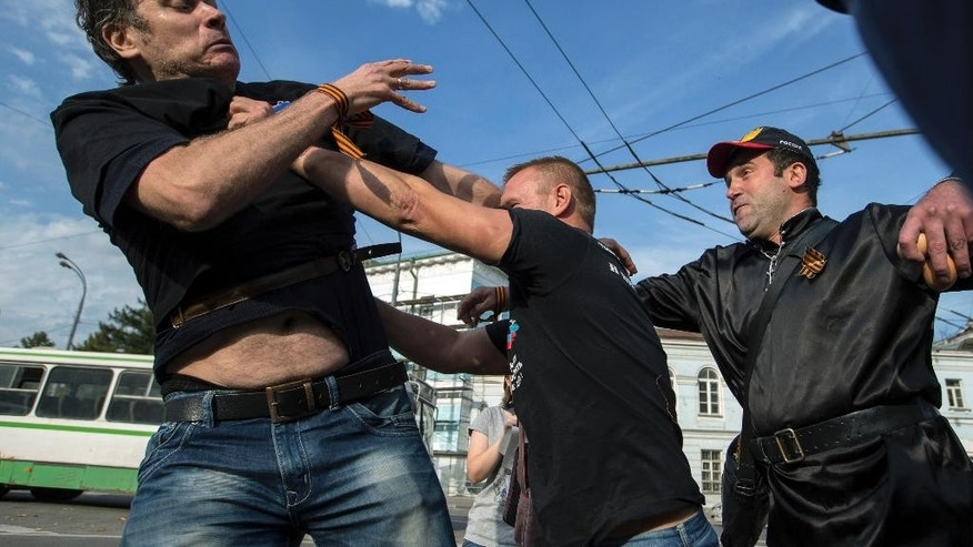 Pro-Putin demonstrators fight between themselves as they discuss about a nearby anti-war demonstration in Moscow, Russia, Sunday, Sept. 27, 2015.  Unsanctioned anti-war protests were held in Russian cities Moscow and St. Petersburg on Sunday. (AP Photo/Pavel Golovkin)