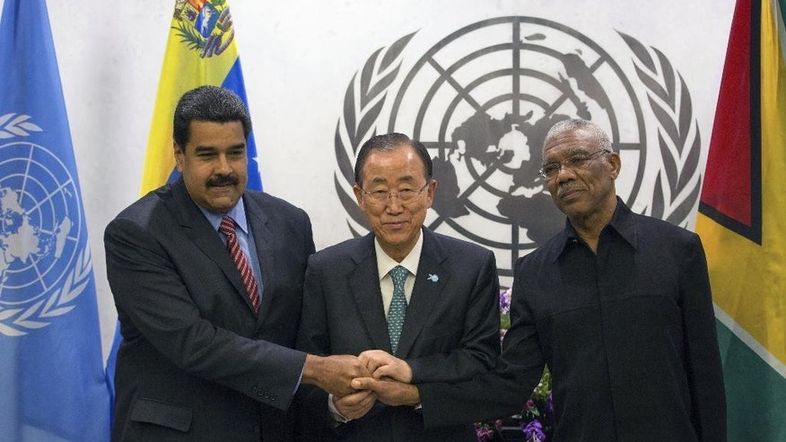 United Nations Secretary-General Ban Ki-moon, center, joins hands with Venezuelan President Nicolas Maduro Moros, left, and Guyanese President David Arthur Granger at the United Nations headquarters Sunday, Sept. 27, 2015. (AP Photo/Kevin Hagen)