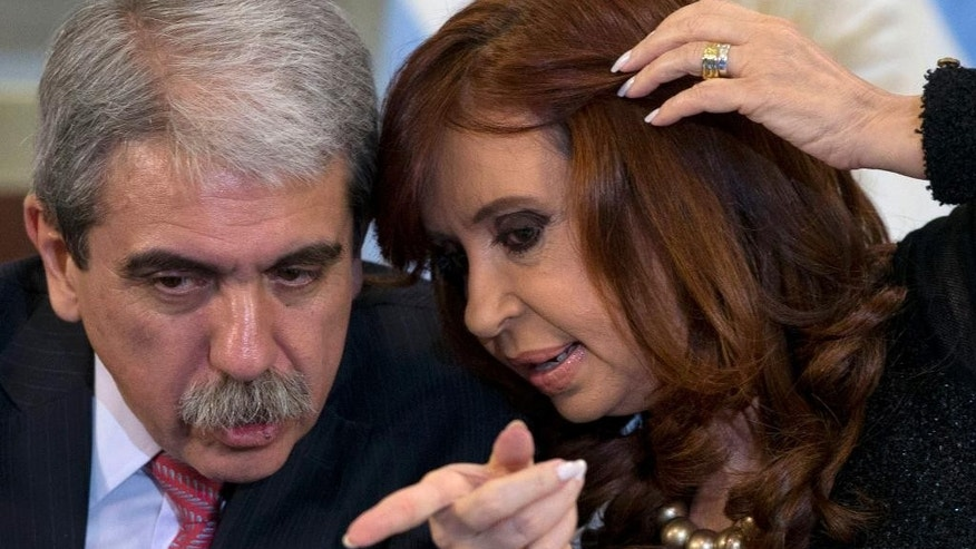 In this Thursday, Aug. 20, 2015 photo, Argentina's Cabinet chief Anibal Fernandez, left, and President Cristina Fernandez talk during a ceremony at the government house in Buenos Aires, Argentina. For voters in Argentina, which has suffered periodic financial crises and has the dubious distinction of the largest default in world history, the top issues are crime and the economy, not political corruption. (AP Photo/Natacha Pisarenko)