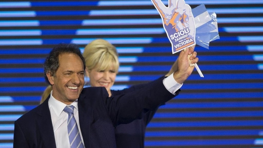 In this Monday, Aug. 10, 2015 photo, Governor of the Buenos Aires province and Presidential candidate Daniel Scioli, left, and his wife Karina Rabolini wave to followers after primaries elections in Buenos Aires, Argentina. When asked about the administration's scandals during a recent interview with The Associated Press, Scioli said the accusations were an indication that the opposition lacked good ideas. (AP Photo/Natacha Pisarenko)