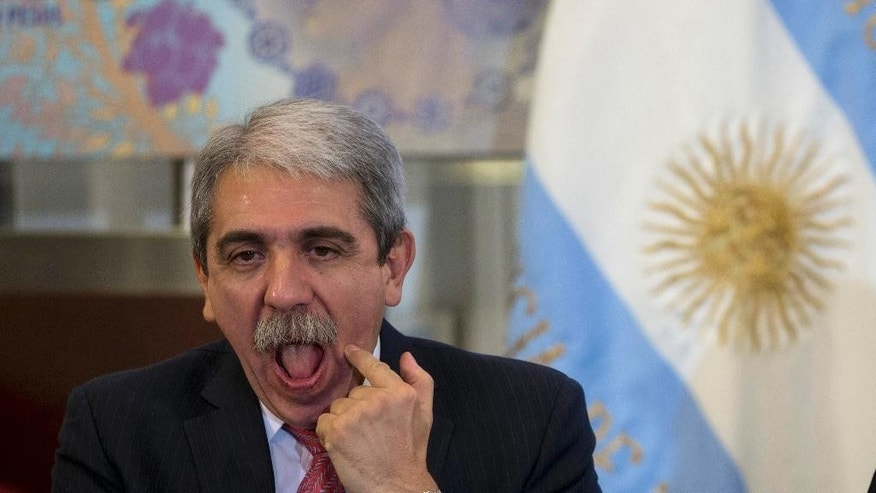In this Thursday, Aug. 20, 2015 photo, Argentina's Cabinet chief Anibal Fernandez gestures during a ceremony at the government house in Buenos Aires, Argentina. During an August jailhouse interview with the Clarin Group, Martin Lanatta, convicted of killing three men allegedly connected to an ephedrine ring, said Fernandez was behind the hit but provided no details. (AP Photo/Natacha Pisarenko)