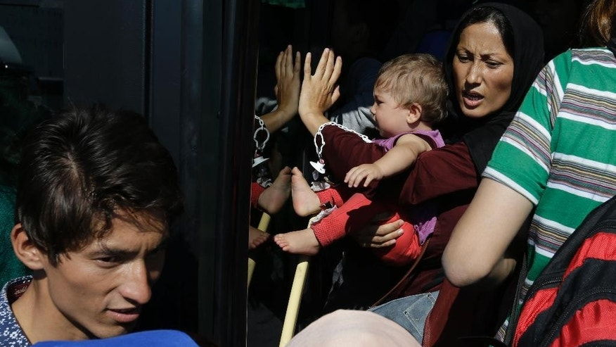 A woman reacts as she tries to board a crowded bus with her baby, transporting them to the metro station, after their arrival from the Greek island of Lesbos at Athens' port of Piraeus, Monday, Sept. 28, 2015. The Greek ferry Elefhterios Venizelos is part of special ferry service for refugees and migrants that carries 2,500 paying passengers. More than 250,000 asylum seekers have passed through Greece so far this year. (AP Photo/Thanassis Stavrakis)