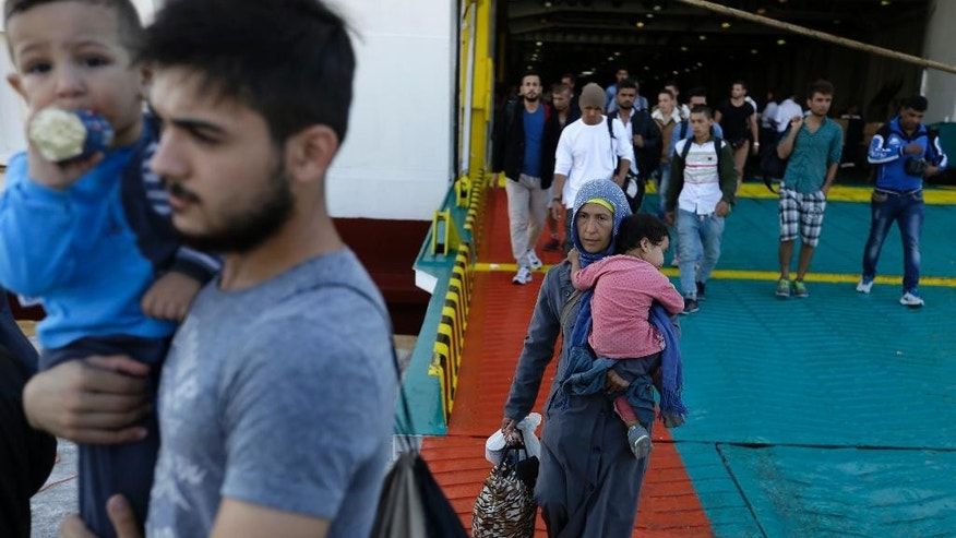 Immigrants and refugees arrive on a ferry from the Greek island of Lesbos at Athens' port of Piraeus, Monday, Sept. 28, 2015. The Greek ferry Elefhterios Venizelos is part of special ferry service for refugees and migrants that carries 2,500 paying passengers. More than 250,000 asylum seekers have passed through Greece so far this year. (AP Photo/Thanassis Stavrakis)