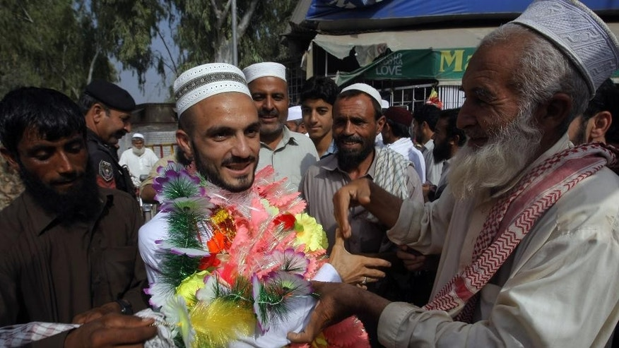 A Pakistani man, center left, is greeted by relatives on his arrival from Saudi Arabia after performing the Muslim hajj pilgrimage, Monday, Sept. 28, 2015 in Peshawar, Pakistan. Pakistan's minister for religious affairs says authorities have tracked down 217 Pakistanis who went missing following last week's stampede that killed more than 700 pilgrims during the hajj in Saudi Arabia. (AP Photo/Mohammad Sajjad)