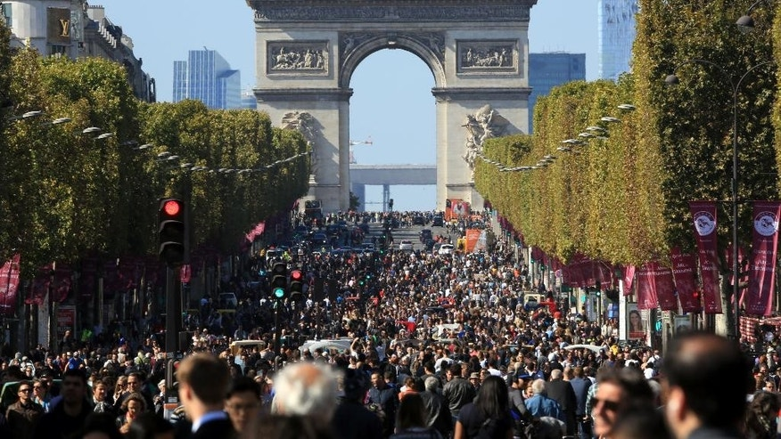 "People walk on the Champs Elysees during the ""day without cars"", in Paris, France, Sunday, Sept. 27, 2015. Pretty but noisy Paris, its gracious Old World buildings blackened by exhaust fumes, is going car-less for a day. Paris Mayor Anne Hidalgo presided over Sunday's ""day without cars,"" two months before the city hosts the global summit on climate change. (AP Photo/Thibault Camus)"