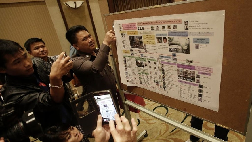 Reporters and photographers take photos of a chart of suspect bombers after a press conference in Bangkok, Thailand, Monday, Sept. 28, 2015. Police have given their most detailed explanation yet of who they believe was behind last month's deadly bombing in Bangkok, for the first time publicly linking one of the suspects to previous explosions. Authorities have said they believe the Aug. 17 bombing, which killed 20 people and injured more than 120, was carried out by a people smuggling gang seeking revenge for having their operation curbed. (AP Photo/Sakchai Lalit)