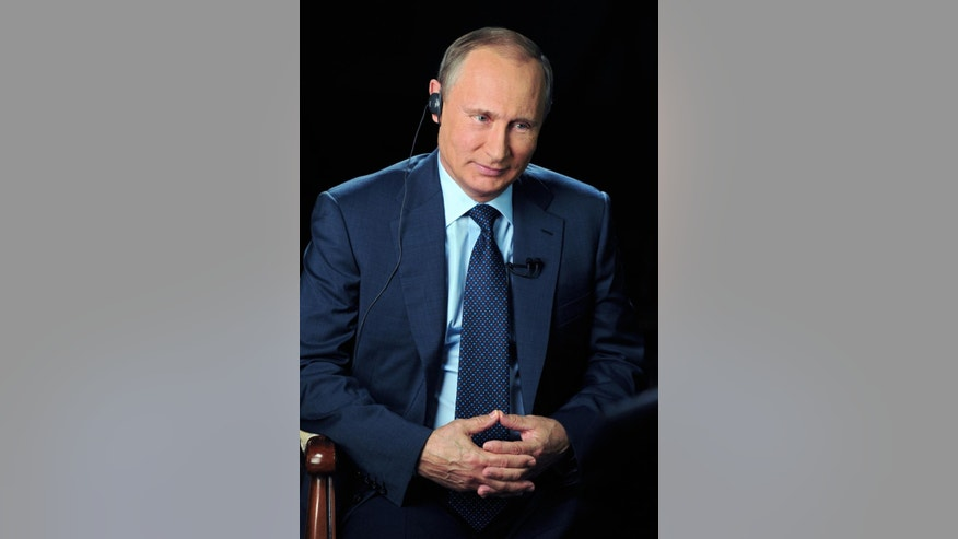In this Sunday, Sept. 20, 2015 photo released on Monday, Sept. 28, 2015 by the Kremlin press service, Russian President Vladimir Putin smiles as he listens to a question during an interview with CBS and PBS in Moscow, Russia. (Mikhail Klimentyev/RIA-Novosti, Kremlin Pool Photo via AP)