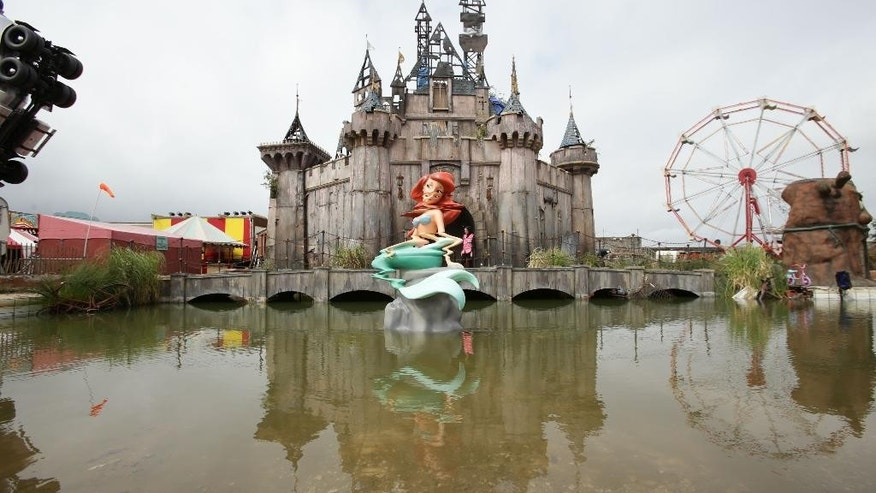 "FILE  - In this Aug. 20, 2015 file photo,  a view of 'Dismaland' , in Western-super-Mare, Somerset, England.  An anarchic amusement park by street artist Banksy that mocked capitalism and consumer culture has brought an economic boom to a faded seaside town. Banksy's Dismaland ""bemusement park"" transformed a derelict outdoor swimming pool in Weston-Super-Mare into a macabre parody of a theme park, complete with a derelict castle, a dead Cinderella and a Grim Reaper in a bumper car. Local officials say the attraction, which closes Sunday, Sept 27, 2015 after five weeks, drew more than 150,000 people to the southwest England town of 75,000. (Yui Mok/PA via AP, File) UNITED KINGDOM OUT"