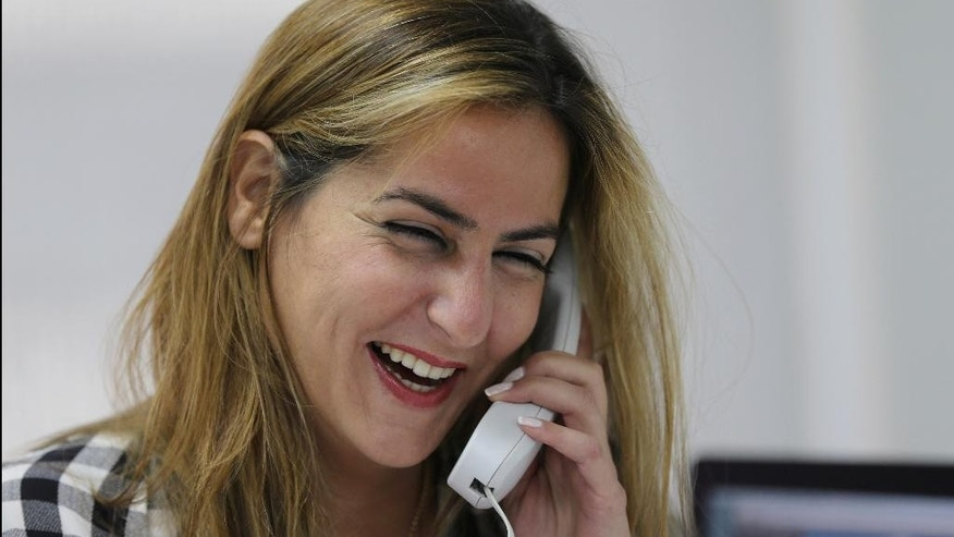 Karma Khayat, the deputy director of a local TV station Al-Jadeed, laughs as she speaks on phone after the U.N.-backed tribunal fined her 10,000 euros ($11,195), at her office in Beirut, Lebanon, Monday, Sept. 28, 2015. A special U.N.-backed tribunal on the assassination of former Lebanese Prime Minister Rafik Hariri has fined the manager of a local TV station for not removing information about identities of confidential witnesses in the long-running probe.(AP Photo/Hussein Malla)
