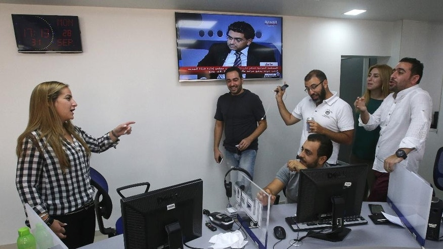 Lebanese Karma Khayat, left, the deputy director of a local TV station Al-Jadeed, speaks with her staff reporters, right, in Beirut, Lebanon, Monday, Sept. 28, 2015. A special U.N.-backed tribunal on the assassination of former Lebanese Prime Minister Rafik Hariri has fined the manager of a local TV station for not removing information about identities of confidential witnesses in the long-running probe.(AP Photo/Hussein Malla)