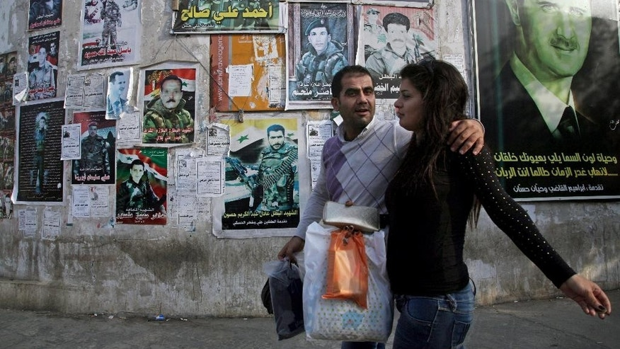 FILE - In this Oct. 28, 2014 file photo, residents walk past posters of slain Syrian soldiers and a poster of Syrian President Bashar Assad, far right, pasted on the wall on a main street in the city of Tartous, the capital of a coastal province in Syria. The country has already been shattered by more than four years of civil war, and with no solution in sight some players on the ground and observers outside have concluded its fate will be to break up along sectarian or regional lines, in a best-case scenario, tenuously held together by a less centralized state. (AP Photo/Diaa Hadid, File)