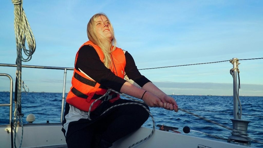 In this Sept. 9, 2015 photo, Annika Holm Nielsen sails in the Oresund strait between Copenhagen and Malmo, Sweden. A 24-year-old Danish woman sails refugees across windy straits to safety in Sweden. A Romanian, whose forebears were driven from their homeland, opens his house to today's migrants. A girl brings pens and paper to migrant children sleeping at a Milan train station. (AP Photo/David Keyton)