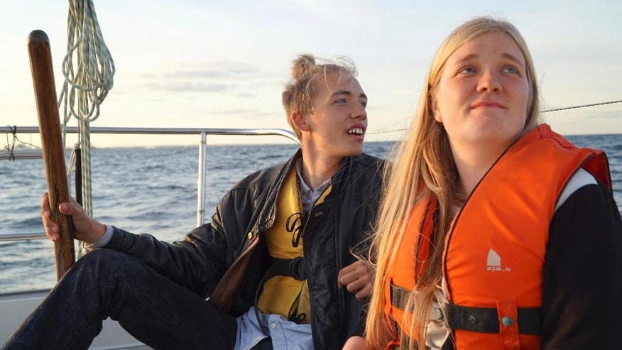 In this Sept. 9, 2015 photo, Annika Holm Nielsen, right, and Calle Vangstrup sail in the Oresund strait between Copenhagen and Malmo, Sweden. A 24-year-old Danish woman sails refugees across windy straits to safety in Sweden. A Romanian, whose forebears were driven from their homeland, opens his house to today's migrants. A girl brings pens and paper to migrant children sleeping at a Milan train station. While European governments string razor wire across borders and argue over asylum rules, ordinary citizens are taking action to cope with an unprecedented inflow of migrants, their generosity offering moments of hope for the newcomers _ and for Europe itself. (AP Photo/David Keyton)