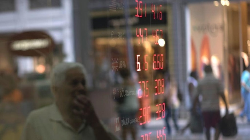 In this Sept. 22, 2015 photo, a man looks at a currency board in Rio de Janeiro, Brazil. The Brazilian currency, the real, has plummeted about 35 percent against the dollar this year, hitting an all-time low in recent days of over 4-to-1. (AP Photo/Felipe Dana)