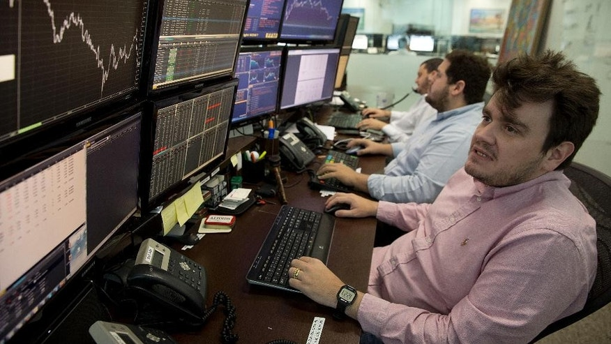 In this Sept. 22, 2015 photo, a broker checks his screens at a brokerage firm in Sao Paulo, Brazil. A strong dollar hikes inflation in Brazil and drastically hurts many of the nation's top firms who hold dollar-denominated debt, principally among them, Petrobras, the country's biggest company.  (AP Photo/Andre Penner)