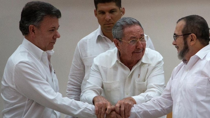 In this Wednesday, Sept. 23, 2015 photo, Cuba's President Raul Castro, center, encourages Colombian President Juan Manuel Santos, left, and Commander the Revolutionary Armed Forces of Colombia or FARC, Timoleon Jimenez to shake hands, in Havana, Cuba. In a joint statement, Santos and the FARC said they have overcome the last significant obstacle to a peace deal by settling on a formula to compensate victims and punish belligerents for human rights abuses. (AP Photo/Desmond Boylan)