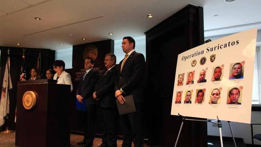 U.S. Justice and FBI officials stands by a poster with photos of the 10 police officers arrested during news conference about charges filed against the Puerto Rican police officers at the United States Attorney's Office in San Juan, Puerto Rico, Tuesday, Sept. 29, 2015. The 10 police officers have been indicted for their alleged participation in a criminal organization, run out of the police department, that used their affiliation with law enforcement to make money through robbery, extortion, manipulating court records and selling illegal narcotics. (AP Photo/Ricardo Arduengo)