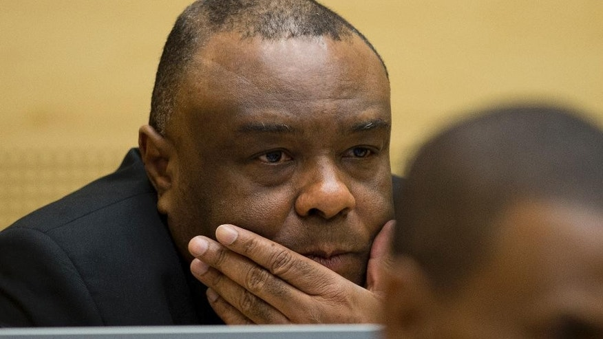 Jean-Pierre Bemba Gombo looks up when sitting in the court room of the International Criminal Court to stand trial with Aime Kilolo Musamba, Jean-Jacques Mangenda Kabongo, Fidele Babala Wandu and Narcisse Arido, on charges including corruptly influencing witnesses by giving them money and instructions to provide false testimony, and presenting false evidence, in The Hague, Netherlands, Tuesday, Sept. 29, 2015. (AP Photo/Peter Dejong, Pool)