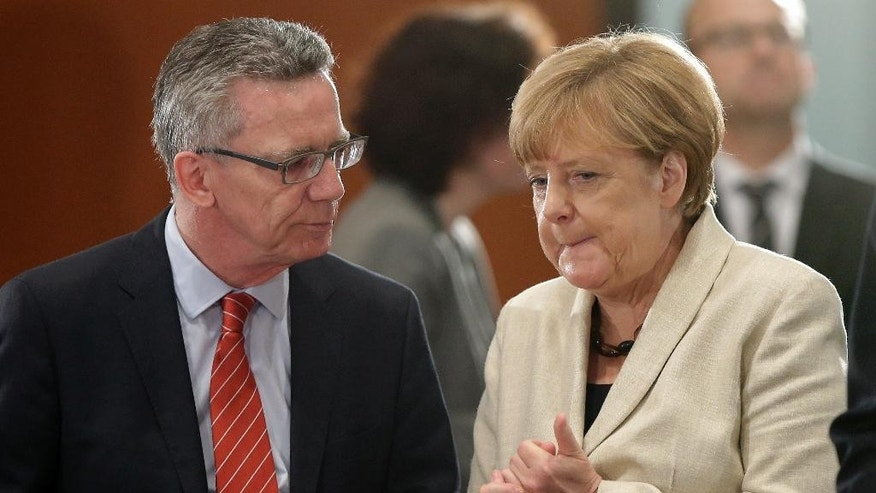 German Chancellor Angela Merkel, right, and German Interior Minister Thomas de Maiziere, left, talk during a meeting of representatives of organizations involved in receiving refugees at the chancellery in Berlin, Germany, Tuesday, Sept. 29, 2015. (AP Photo/Michael Sohn)
