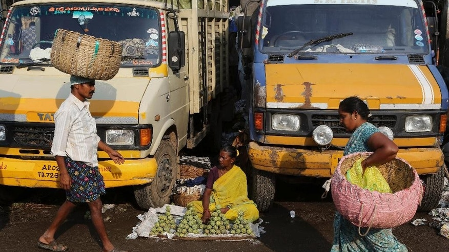 An Indian roadside vendor sits between trucks to sell fruits at a wholesale market in  Bangalore, India, Tuesday, Sept. 29, 2015.  India's central bank on Tuesday cut its key interest rate by half a percentage point, aiming to spur economic growth as inflation cooled to the lowest since November. (AP Photo/Aijaz Rahi)