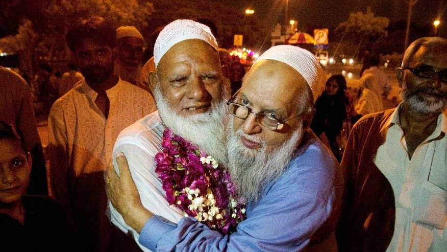A Pakistani man receives his family member who returned from Saudi Arabia after the hajj pilgrimage, at Karachi airport, Pakistan, Monday, Sept. 28, 2015. Pakistan's minister for religious affairs says authorities have tracked down 217 Pakistanis who went missing following last week's stampede that killed hundreds of pilgrims during the hajj in Saudi Arabia. (AP Photo/Shakil Adil)