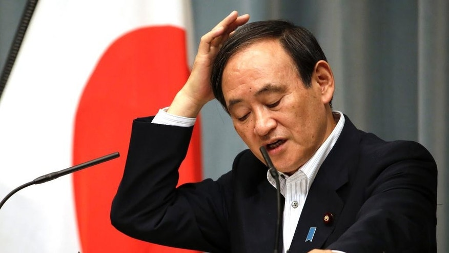 Japan's Chief Cabinet Secretary Yoshihide Suga answers a question from a journalist during a press conference at the prime minister's official residence in Tokyo, Wednesday, Sept. 30, 2015. China is holding two Japanese men on suspicion of spying, Japanese media reported Wednesday. One man was picked up in May near military facilities in coastal Zhejiang province and the other near the border with North Korea about the same time, Japan's leading newspapers and television stations said. Suga told reporters that Japan does its utmost to protect citizens abroad, but that he would not discuss specific cases. (AP Photo/Eugene Hoshiko)