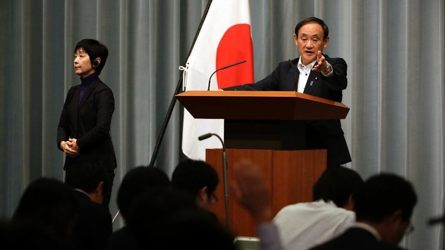 Japan's Chief Cabinet Secretary Yoshihide Suga receives a question from a journalist during a press conference at the prime minister's official residence in Tokyo, Wednesday, Sept. 30, 2015. China is holding two Japanese men on suspicion of spying, Japanese media reported Wednesday. One man was picked up in May near military facilities in coastal Zhejiang province and the other near the border with North Korea about the same time, Japan's leading newspapers and television stations said. Suga told reporters that Japan does its utmost to protect citizens abroad, but that he would not discuss specific cases. (AP Photo/Eugene Hoshiko)