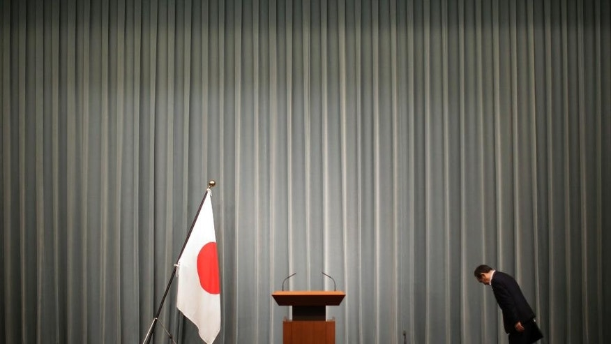Japan's Chief Cabinet Secretary Yoshihide Suga bows toward the Japanese national flag prior to a press conference at the prime minister's official residence in Tokyo, Wednesday, Sept. 30, 2015. China is holding two Japanese men on suspicion of spying, Japanese media reported Wednesday. One man was picked up in May near military facilities in coastal Zhejiang province and the other near the border with North Korea about the same time, Japan's leading newspapers and television stations said. Suga told reporters that Japan does its utmost to protect citizens abroad, but that he would not discuss specific cases. (AP Photo/Eugene Hoshiko)