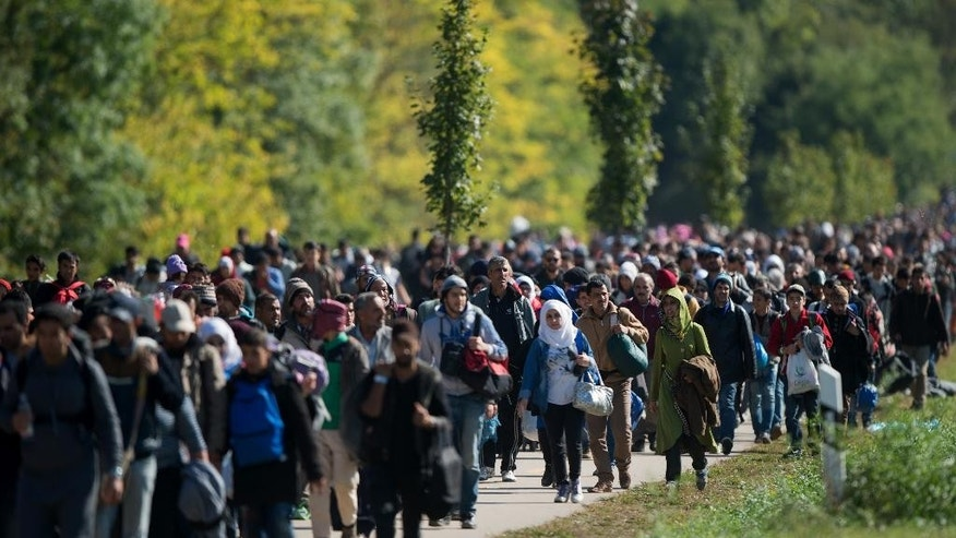 Migrants walk to the Austrian - Hungarian border near Hegyeshalom, Hungary,  on Monday Sept. 28, 2015. (AP Photo/Christian Bruna)