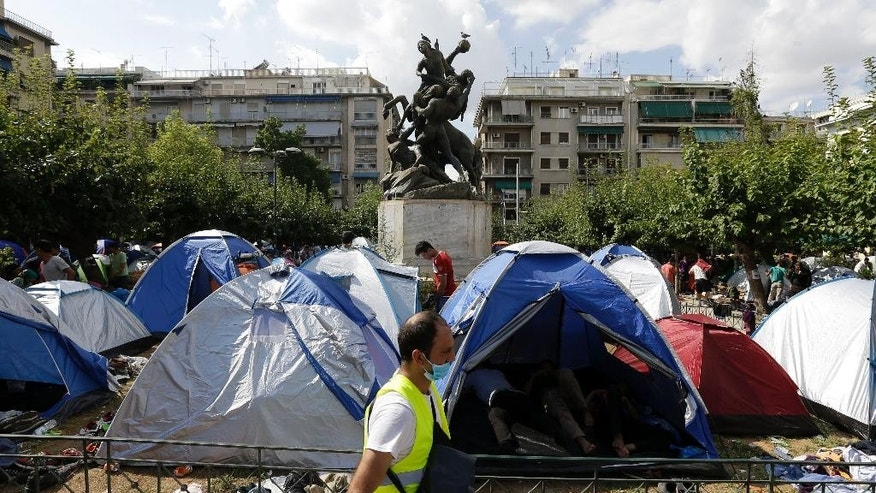 A municipality worker clears the area around tents at Victoria square, where many migrants stay temporarily before trying to continue their trip to more prosperous northern European countries, in Athens, Monday, Sept. 28, 2015. More than 250,000 asylum seekers have passed through Greece so far this year. The vast majority are Syrians, Iraqis and Afghans fleeing conflict at home. (AP Photo/Thanassis Stavrakis)