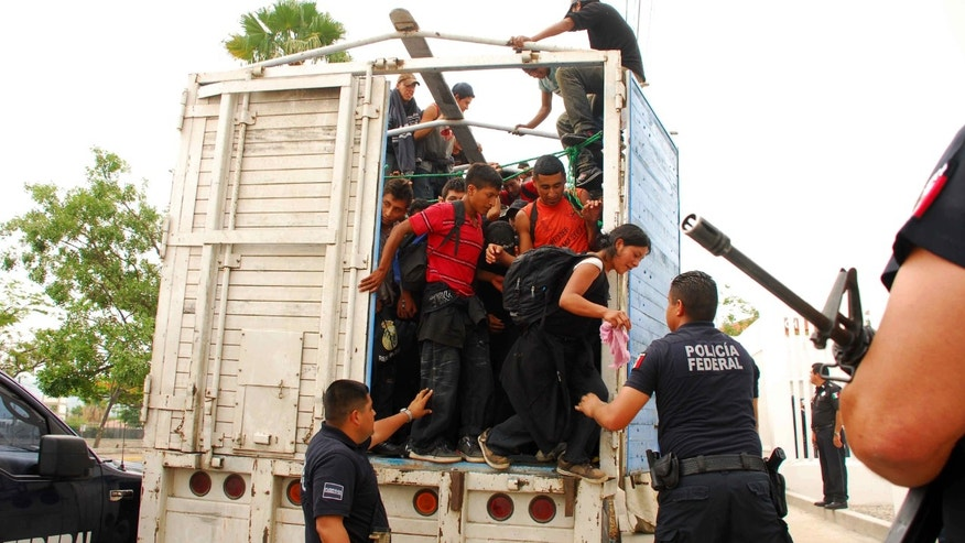 Migrants jump out of a tractor trailer as Mexican federal police watch at police headquarters in Tuxtla Gutierrez, Mexico, Sunday June 12, 2011. (AP Photo/Alejandro Estrada)