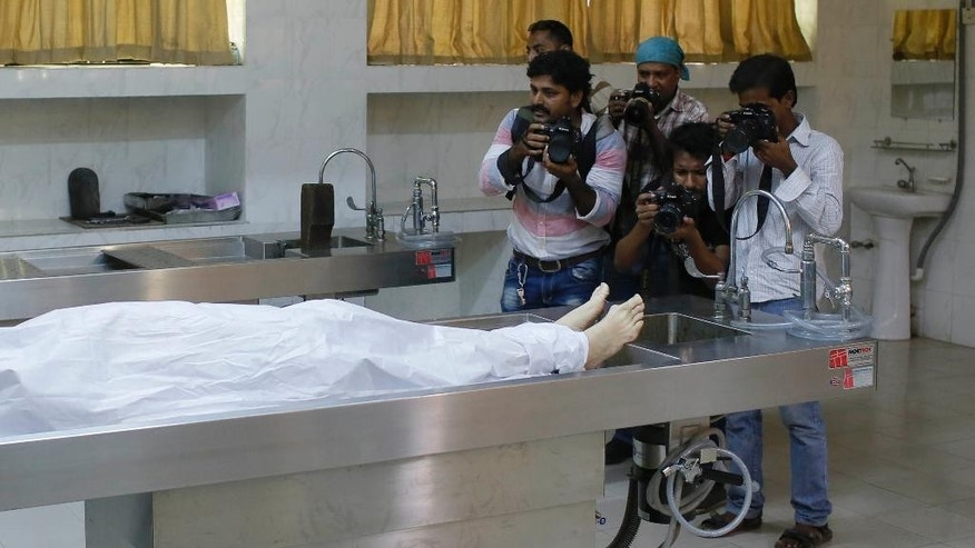 Journalists take photographs as the body of Italian citizen Cesare Tavella who was gunned down by unidentified assailants is kept at a hospital morgue in Dhaka, Bangladesh, Tuesday, Sept. 29, 2015. The Islamic State militant group claimed responsibility for gunning down the Italian citizen on the street in the diplomatic quarter of Bangladesh's capital, according to an intelligence group monitoring jihadist threats. (AP Photo/ A.M. Ahad)