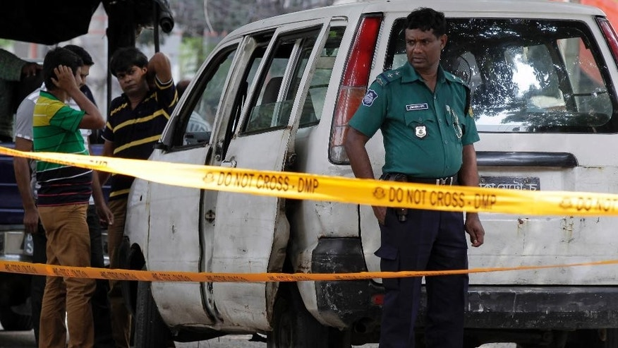 Members of Bangladeshi police and detective branch stand by the site where Italian citizen Cesare Tavella was gunned down by unidentified assailants in Dhaka, Bangladesh, Tuesday, Sept. 29, 2015. The Islamic State militant group claimed responsibility for gunning down the Italian citizen on the street in the diplomatic quarter of Bangladesh's capital, according to an intelligence group monitoring jihadist threats. (AP Photo/ A.M. Ahad)