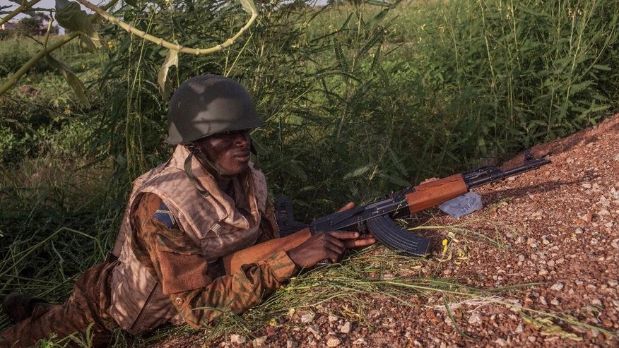 Burkina Faso government soldier holds his position during a patrol of a suburb taking control from the soldiers that took part in a coup in Ouagadougou, Burkina Faso, on Tuesday, Sept. 29, 2015.  Burkina Faso's army stepped up the pressure Tuesday against those behind last week's short-lived coup, surrounding the barracks of coup plotters and arresting a former high-ranking minister accused of collaborating with the mutinous soldiers.(AP Photo/Theo Renaut)