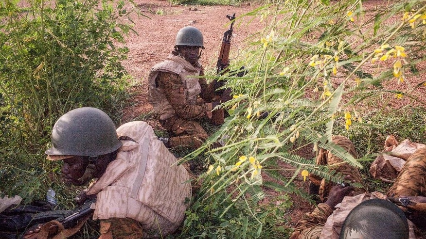 Burkina Faso government soldiers take cover as they patrol a suburb taking control from the soldiers that took part in a coup in Ouagadougou, Burkina Faso, on Tuesday, Sept. 29, 2015.  Burkina Faso's army stepped up the pressure Tuesday against those behind last week's short-lived coup, surrounding the barracks of coup plotters and arresting a former high-ranking minister accused of collaborating with the mutinous soldiers. (AP Photo/Theo Renaut)
