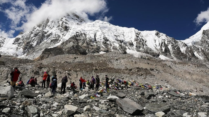 FILE- In this Sept. 27, 2015 file photo, trekkers rest at Everest Base Camp, Nepal. Mohan Sapkota, a spokesman for the Himalayan country's ministry of tourism said Tuesday, Sept. 29, 2015, that Nepal is considering placing age and fitness limits for people who want to climb Mount Everest. Last week Japanese climber Nobukazu Kuriki, who had lost nine fingers to frostbite, abandoned his fifth unsuccessful attempt to scale Everest. Everest climbing permits earn the impoverished nation millions of dollars but the government has come under criticism after a series of disasters over the last few years.  (AP Photo/Tashi Sherpa, file)